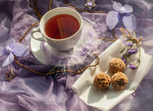 A cup of tea and chocolate sweets on a violet delicate tulle fabric Stock Photo