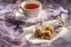 A cup of tea and chocolate sweets on a violet delicate tulle fabric Royalty Free Stock Photos