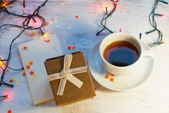 A cup of tea, a Christmas garland with lights and a gift box on a light background. A Christmas gift. Royalty Free Stock Photo