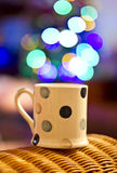 Cup of tea and Christmas tree bokeh. Cuppa on the chair and Christmas tree bokeh on the background. Magic Cuppa Royalty Free Stock Photos