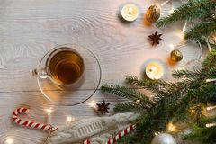 Cup of tea with christmas tree and candles. Christmas composition. Cup of hot fruit tea and Christmas candy canes on white wooden table. Candles and Christmas royalty free stock photography