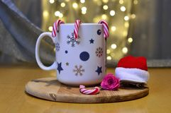 A cup of tea in christmas version with hat of santa claus and candy canes stock image