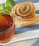 Cup of tea with cinnamon Danish bun Stock Images
