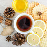 Cup of tea with cinnamon, honey, pinecone, ginger, badian and waffles Stock Photo