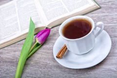 A cup of tea with cinnamon and purple tulip Royalty Free Stock Photos