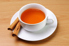 Cup of tea with cinnamon sticks. Served on a table Stock Images