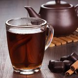 Cup of tea with cinnamon sticks and teapot Royalty Free Stock Photo