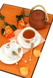 Cup of tea, clay teapot and roses Stock Images