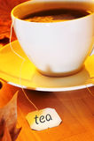 Cup of tea. Closeup of a cup with a tea bag being steeped, on a wooden table Stock Images