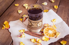 Cup of tea in coaster, dried oranges, dried rose petals on wooden background Stock Photos