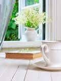 A cup of tea or coffee and a book on a white wooden antique retro table and a bouquet of lily-of-the-valley flowers on a window si