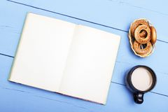 Cup tea, coffee and cookies, book with clean sheet on wooden table. Template copy space.  Royalty Free Stock Images