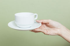 Cup of tea or coffee in hand Stock Photos