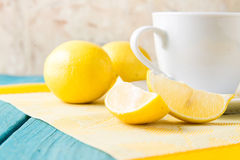 Cup of tea / coffee & lemons. Cup of coffee / hot tea drink / beverage with sliced and whole lemons on yellow placemat table setting Stock Images