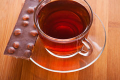 Cup (tea, coffee) and slice. Glass cup with (coffee, tea) and piece of chocolate with nuts (hazelnuts, peanuts), close-up against wooden table Royalty Free Stock Photo