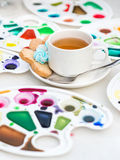 Cup with tea and cookie surrounded watercolor palette Stock Image