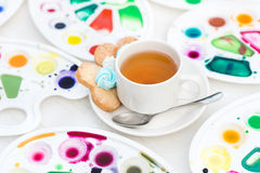 Cup with tea and cookie surrounded watercolor palette Stock Images