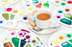 Cup with tea and cookie surrounded watercolor palette Stock Photography