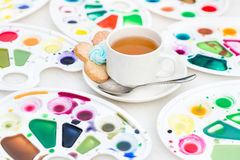Cup with tea and cookie surrounded watercolor palette Stock Photo