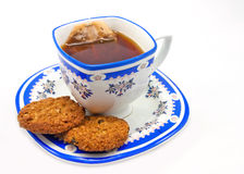 A cup of tea and cookies. Image of black tea in saucer and cookies in plate Stock Images
