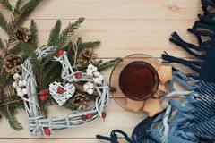 Cup of tea with cookies asterisks with a Christmas wreath heart of winter berries and blue with a white blanket. Cup of tea with cookies asterisks with Christmas royalty free stock photos