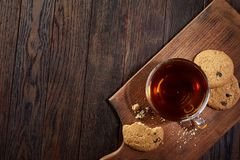 Cup of tea with cookies on a cutting board on a wooden background, top view. A transparent glass cup of tea with delicious chocolate chips cookies on a rough Stock Photography