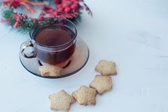 Cup of tea with cookies on a light textural background and a Christmas wreath on the plan. Dark glass cup with a saucer with tea and cookies on a light textural stock images