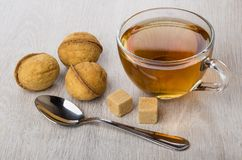 Cup of tea, cookies in form nut, sugar and teaspoon. Cup of tea, cookies with stuffed in form nut, sugar and teaspoon on wooden table Royalty Free Stock Photography