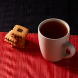 Cup of Tea with Cookies on style red and black background stock photography