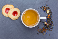 Cup of tea with cookies, sugar and loose leaves. On black slate Stock Images