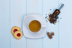 Cup of tea with cookies, sugar and loose leaves. On wooden table Royalty Free Stock Photos