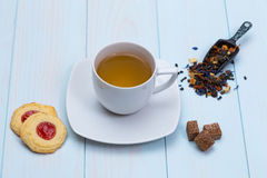 Cup of tea with cookies, sugar and loose leaves. On wooden table Royalty Free Stock Photography