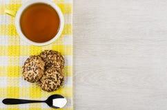 Cup of tea, cookies and teaspoon on yellow napkin Stock Photos