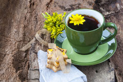 A cup of tea with cookies on a wooden background. A cup of tea, baking cookies,on wood background and yellow flowers Stock Photography