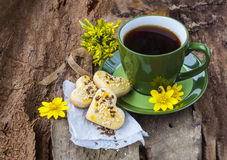 A cup of tea with cookies on a wooden background. A cup of tea, baking cookies,on wood background and yellow flowers,ladybug Royalty Free Stock Photo