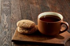Cup of tea with cookies on a wooden cutting board on vintage background, top view. Cup of tea with chocolate chips cookies on a wooden cutting board over vintage Stock Images