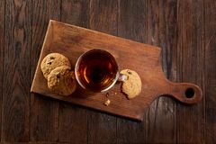 Cup of tea with cookies on a wooden cutting board on vintage background, top view. Cup of tea with chocolate chips cookies on a wooden cutting board over vintage Royalty Free Stock Photos