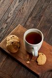 Cup of tea with cookies on a wooden cutting board on vintage background, top view. Cup of tea with chocolate chips cookies on a wooden cutting board over vintage Royalty Free Stock Photography