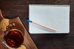 Cup of tea with cookies, workbook and a pencil on a wooden background, top view. A white inside and brown outside porcelain cup of tea with tasty chocolate chips Stock Image