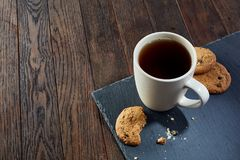 Cup of tea with cookies, workbook and a pencil on a wooden background, top view. A white inside and brown outside porcelain cup of tea with tasty chocolate chips Royalty Free Stock Photography