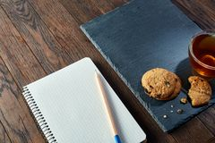 Cup of tea with cookies, workbook and a pencil on a wooden background, top view. A white inside and brown outside porcelain cup of tea with tasty chocolate chips Stock Photos