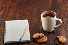 Cup of tea with cookies, workbook and a pencil on a wooden background, top view. A white inside and brown outside porcelain cup of tea with tasty chocolate chips Royalty Free Stock Images