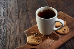 Cup of tea with cookies, workbook and a pencil on a wooden background, top view. A white inside and brown outside porcelain cup of tea with tasty chocolate chips Stock Photography