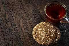 Cup of tea with a couple of cookies on a wooden background, top view, selective focus. A transparent glass cup of tea with a couple of tasty cookies on a a dark Royalty Free Stock Photography
