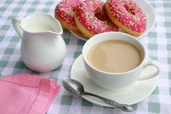 A cup of tea with cream, a creamer, a plate with pink donuts stock photography