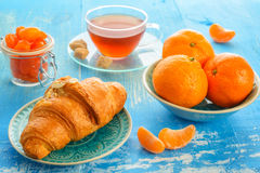 Cup of tea, croissant and mandarines Stock Photos