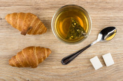 Cup with tea, croissants, lumpy sugar and teaspoon on table Royalty Free Stock Images