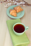 Cup of tea and croissants near blossoming branches Royalty Free Stock Photography
