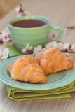 Cup of tea and croissants near blossoming branches Stock Photos