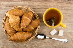 Cup with tea, croissants in wicker basket, sugar and teaspoon Stock Images